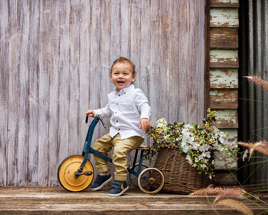 cute-toodler-on-vintage-trike-outdoor-studio.jpg